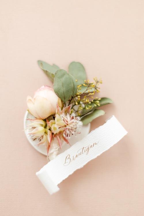 Hochzeitsfotograf Berlin: Hochzeitsdetails Bild mit Anstecker vom Bräutigam - Fine Art Papeterie